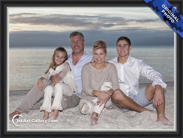 A photo of a family sitting on the beach