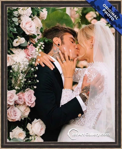 Photo of a wedding couple kissing in flowers